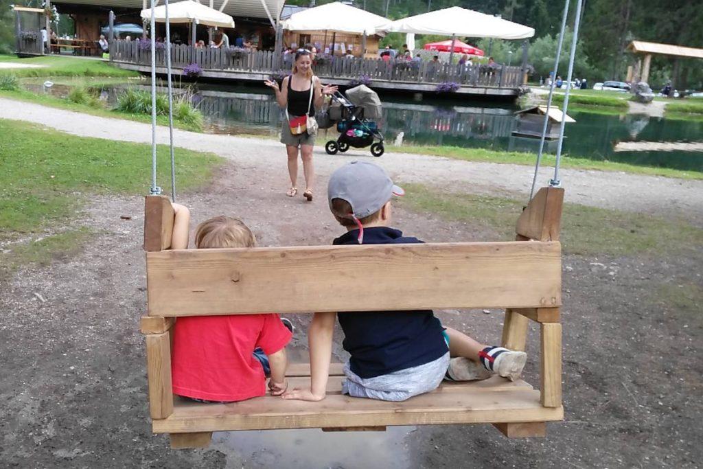 bambini di spalle su un'altalena grande come una panca. Di fronte la mamma li aspetta a braccia aperte