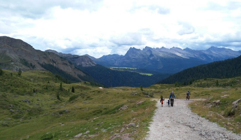 famiglia che cammina di spalle su sentiero di montagna