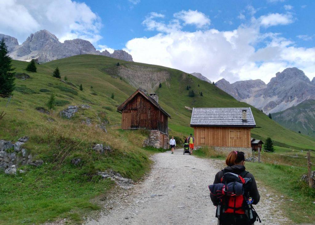 sentiero attraverso case in legno e montagne sullo sfondo
