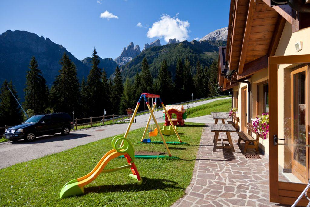 Ingresso del Residence con giochi e Pale di San Martino sullo sfondo