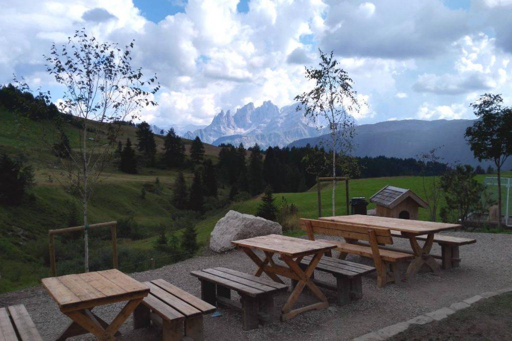 tavoli in legno con Dolomiti sullo sfondo con cielo nuvoloso