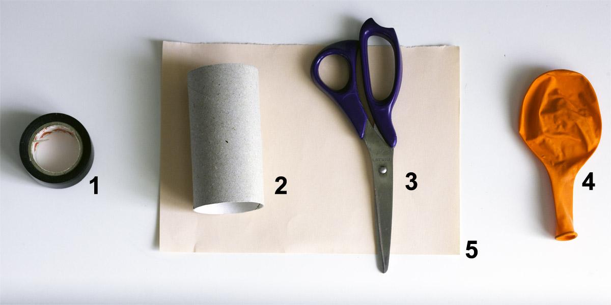 nastro isolante, cartoncino della carta igienica, forbici, palloncino e foglio rosa disposti su un tavolo bianco, visti dall'alto