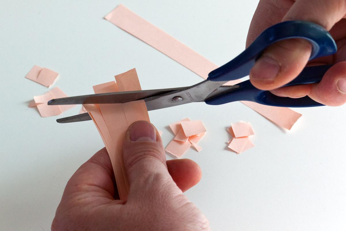 Forbice che taglia le listarelle di carta per fare coriandoli