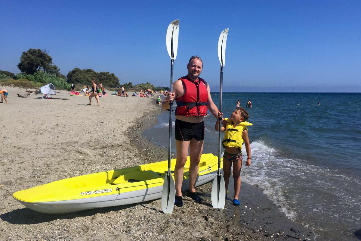 padre e figlio sul in riva al mare con giubbotto salvagente e remi in mano con canoa gialla dietro di loro