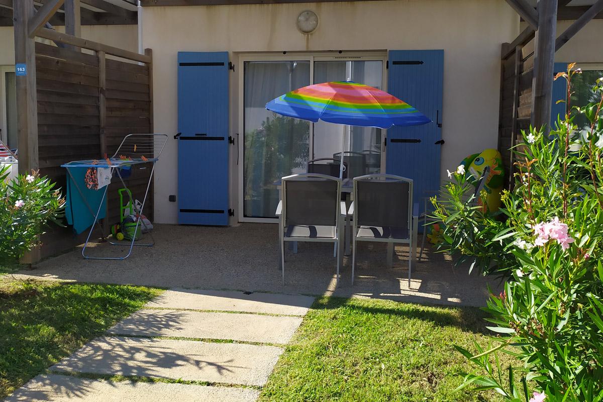 vista di un giardino e di un tavolo con ombrellone arcobaleno di un residence