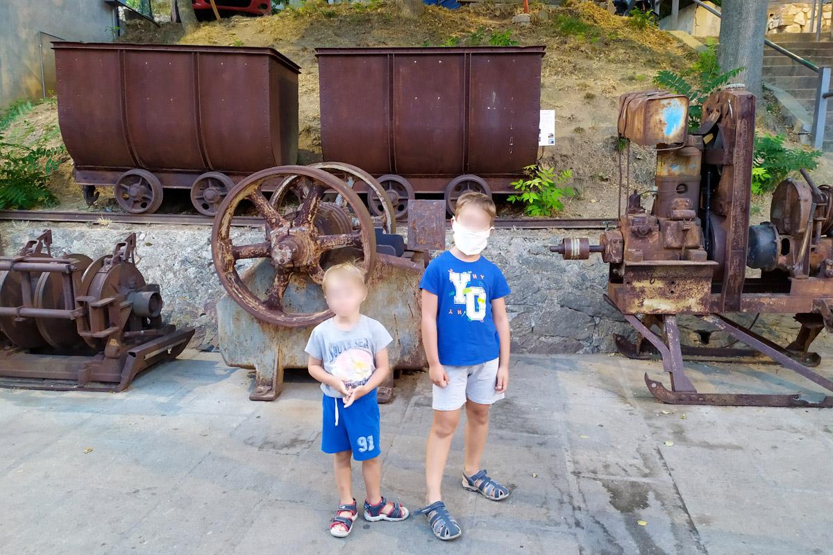 carrelli di una miniera lungo la strada di un paese, bambini