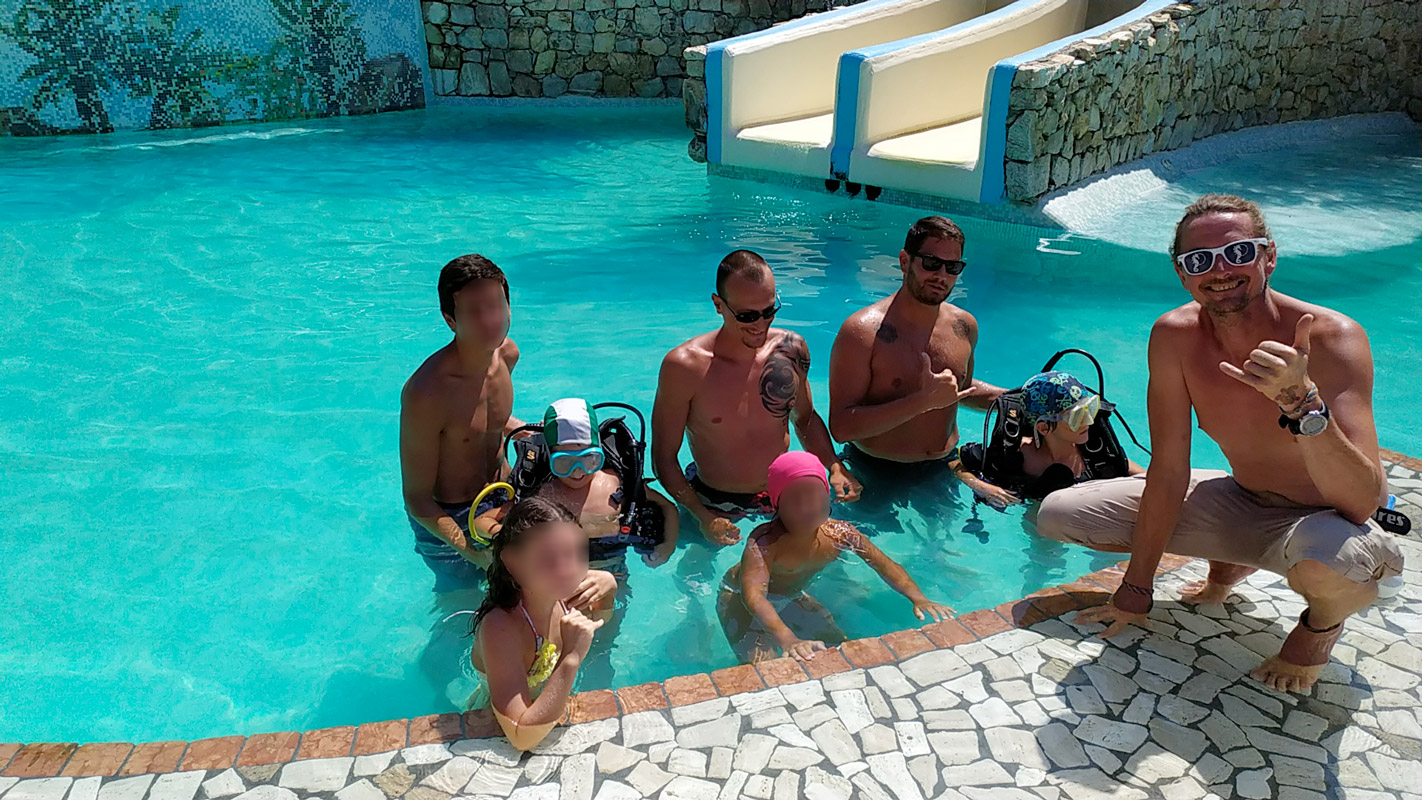 Istruttori di diving con bambini per una dimostrazione in piscina