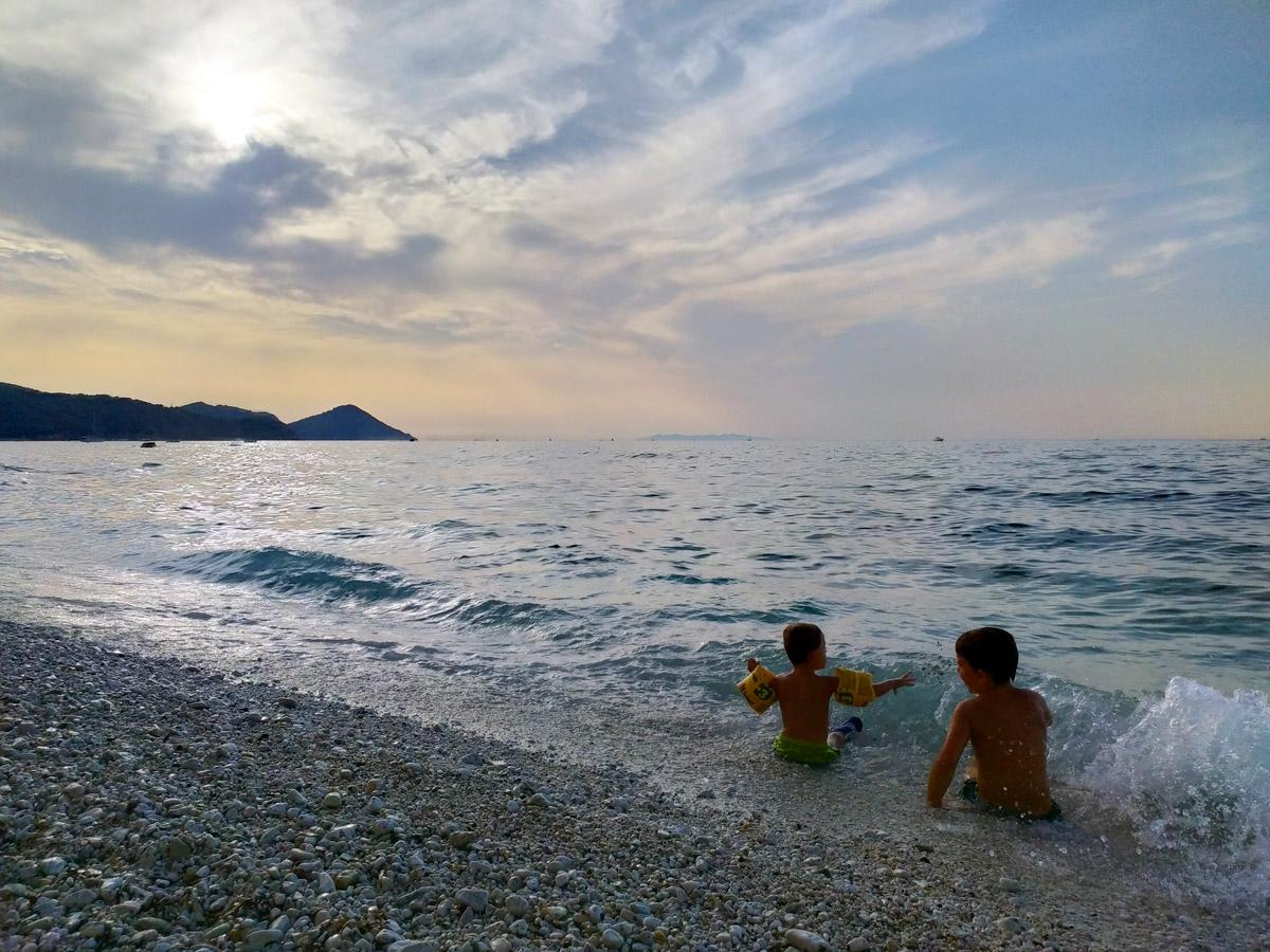 bimbi seduti in riva al mare al tramonto che giocano con le onde