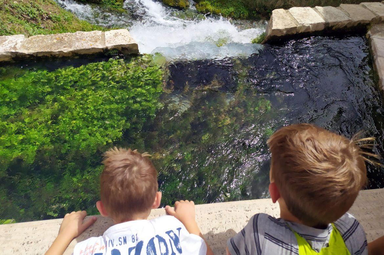bimbi che guardano una vasca di acqua con cascatelle