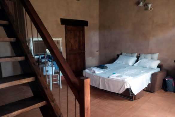Camera con divano letto aperto e sulla sinistra rampa di scale che porta al piano superiore
