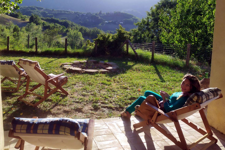 Donna su sdraio che ride e di fronte c'è il panorama del monte Subasio