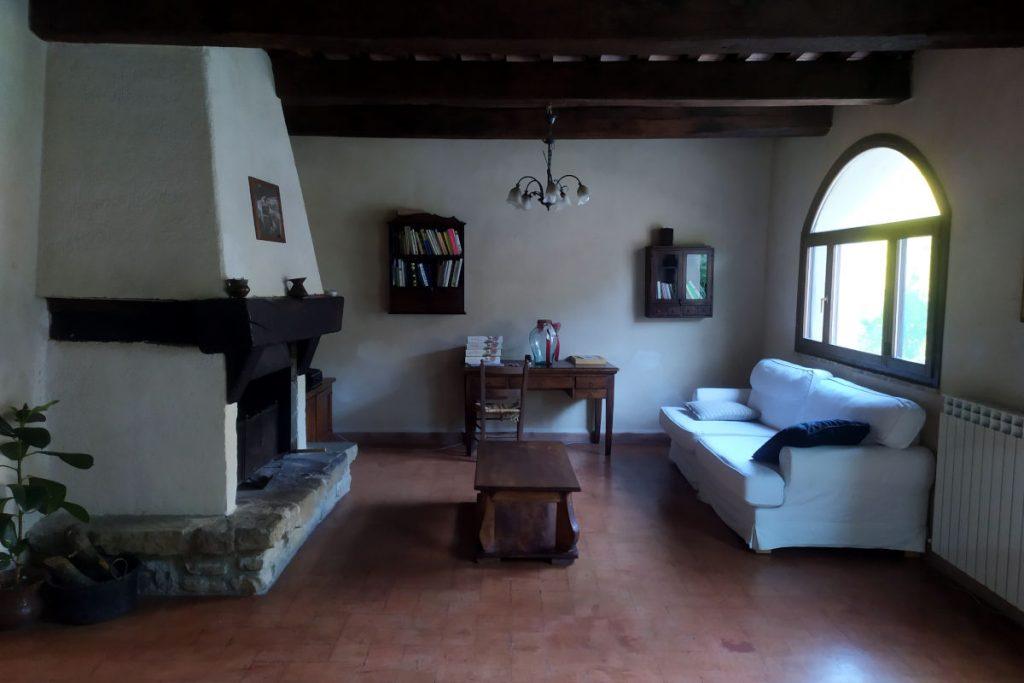 Vista di un salone di un casale con un divano bianco sulla destra e un grande camino a sinistra